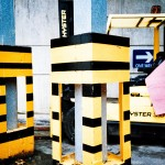 Yellow and black barriers and a fork lift truck